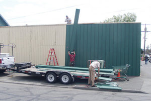 Installing salvaged metal roofing as siding at The RE Store