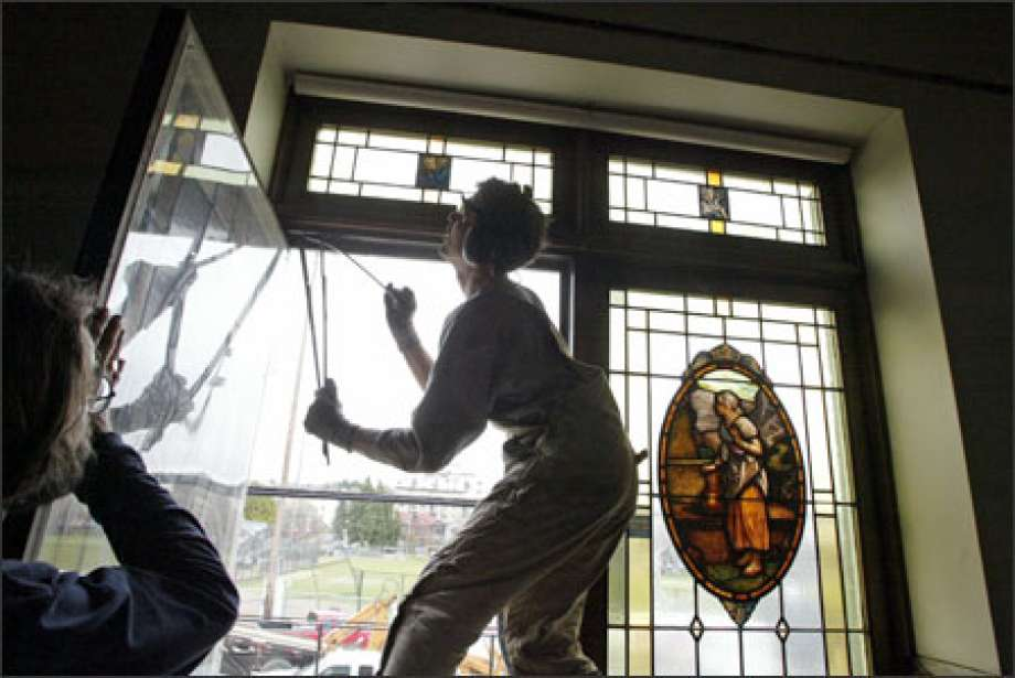 RE Store staff removing a stained glass window